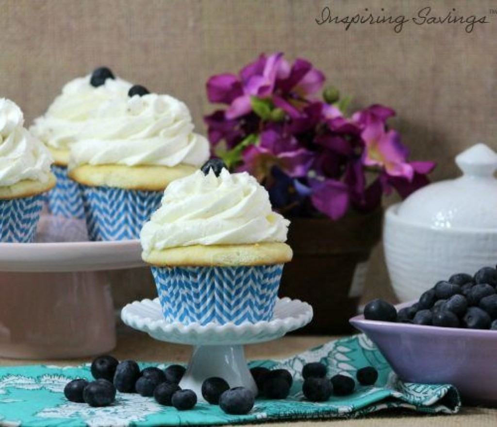 vanilla cupcakes with buttercream frosting and fresh blueberries on table
