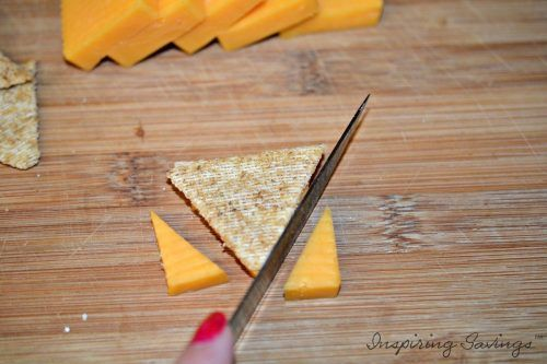 Knife cutting cheese on cutting board