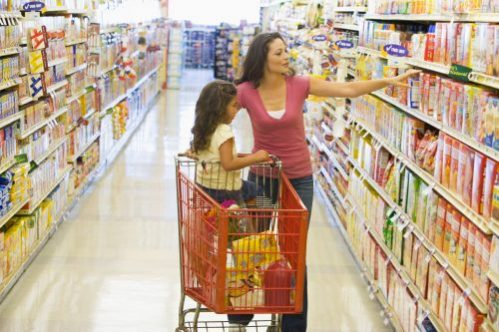 Lady with child in shopping cart at grocery store