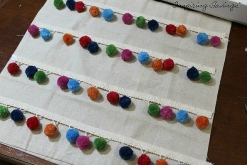 placing pom poms on pillow covers in rows