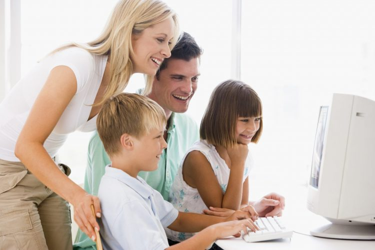 Family on computer together - Teaching Kids about money & Budgeting