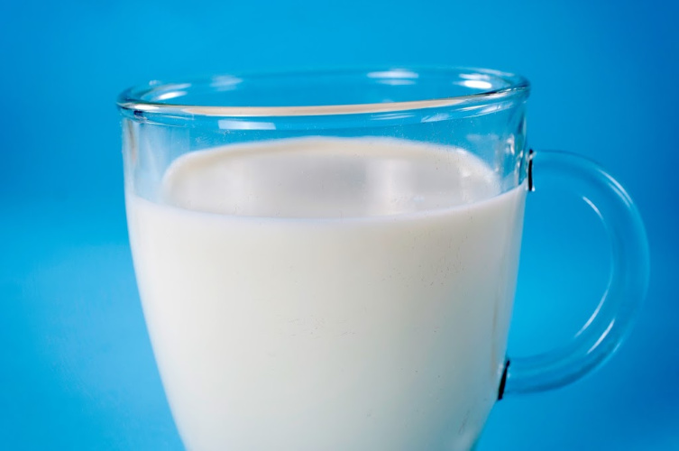 Glass of milk on the light blue background