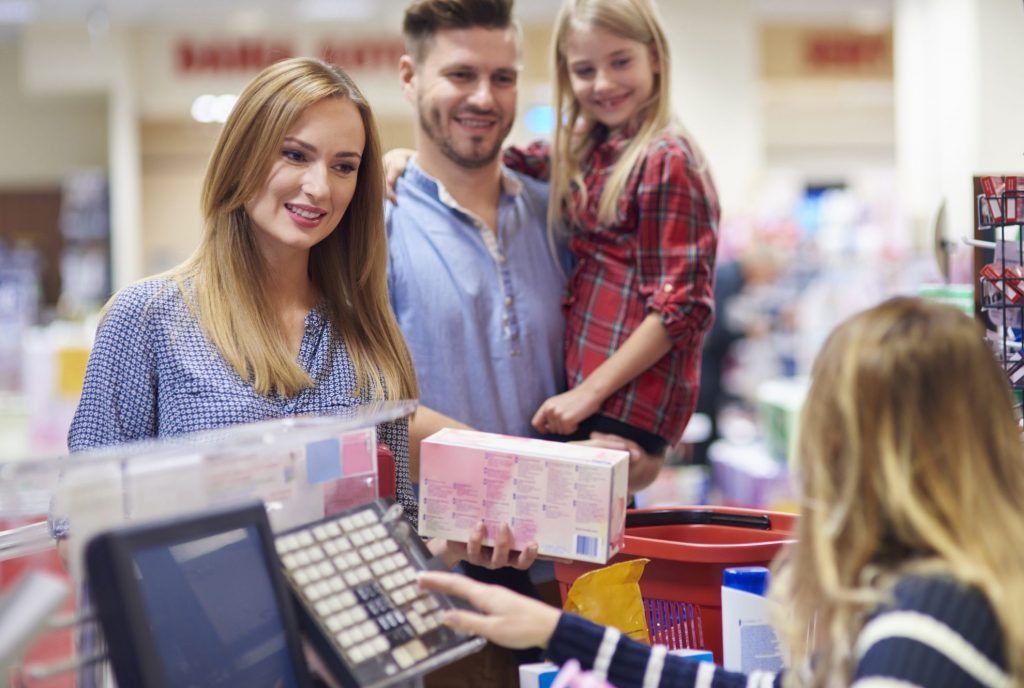 couple at checkout using coupons - is couponing worth it