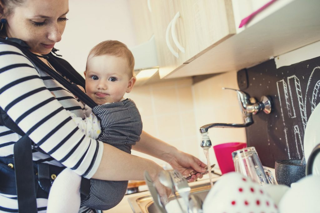 Mom with infant cleaning dishes at sink - infant hand me downs