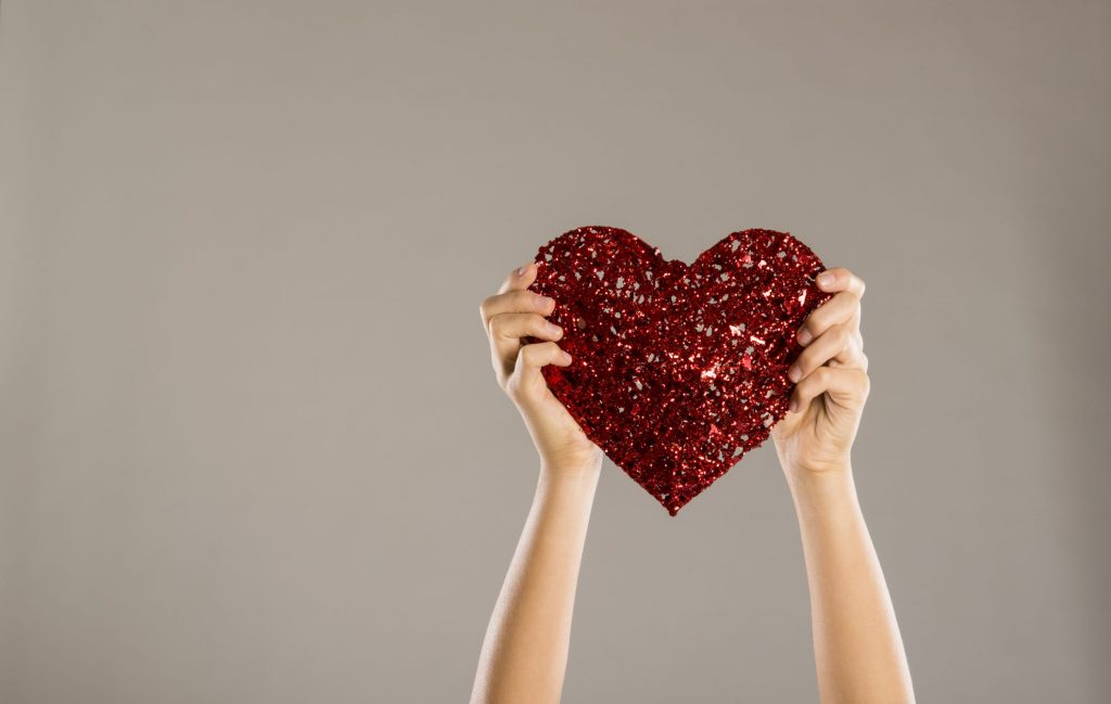 Sparkly heart being held by hands- Giving back - Impact of couponing