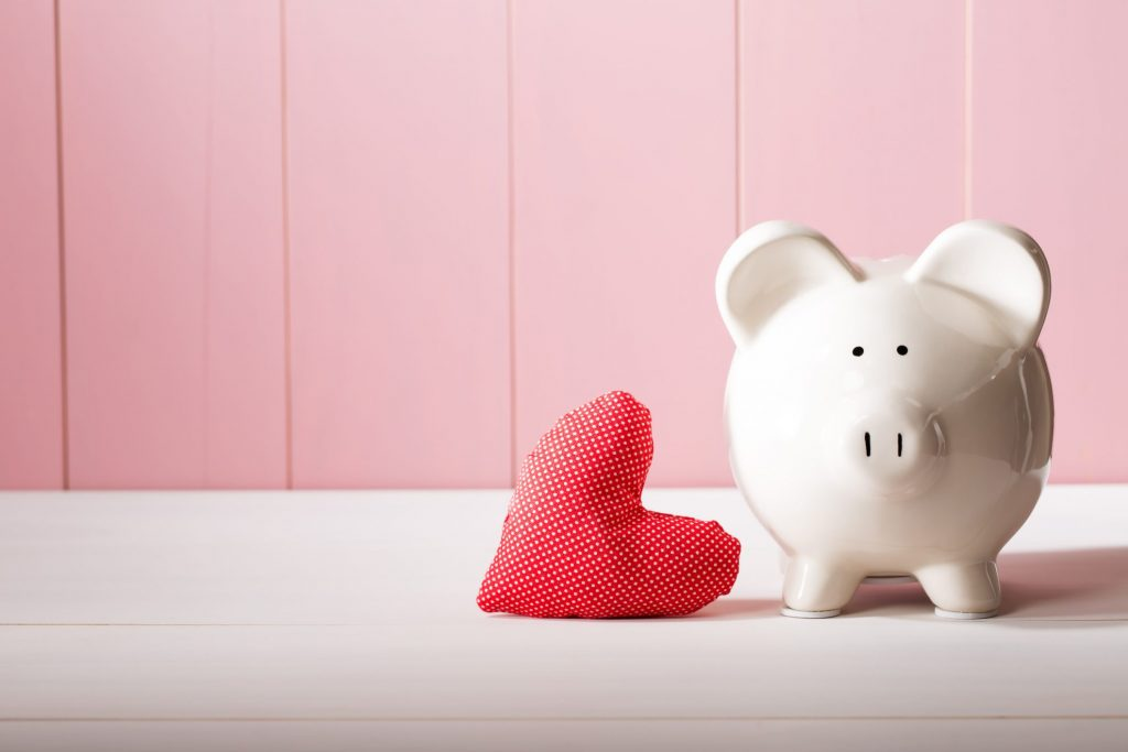 Piggy bank with pink background - saving money - impact of couponing