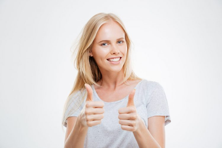 Woman giving thumbs up - impact of couponing sense of accomplishment