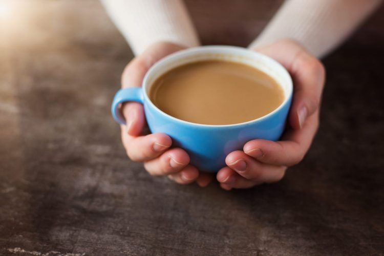 coffee in blue cup being held by two hands