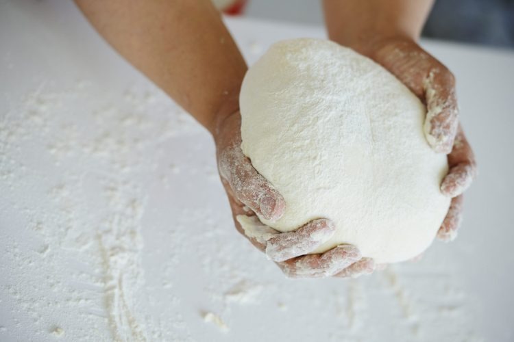 Two hands holding bread dough