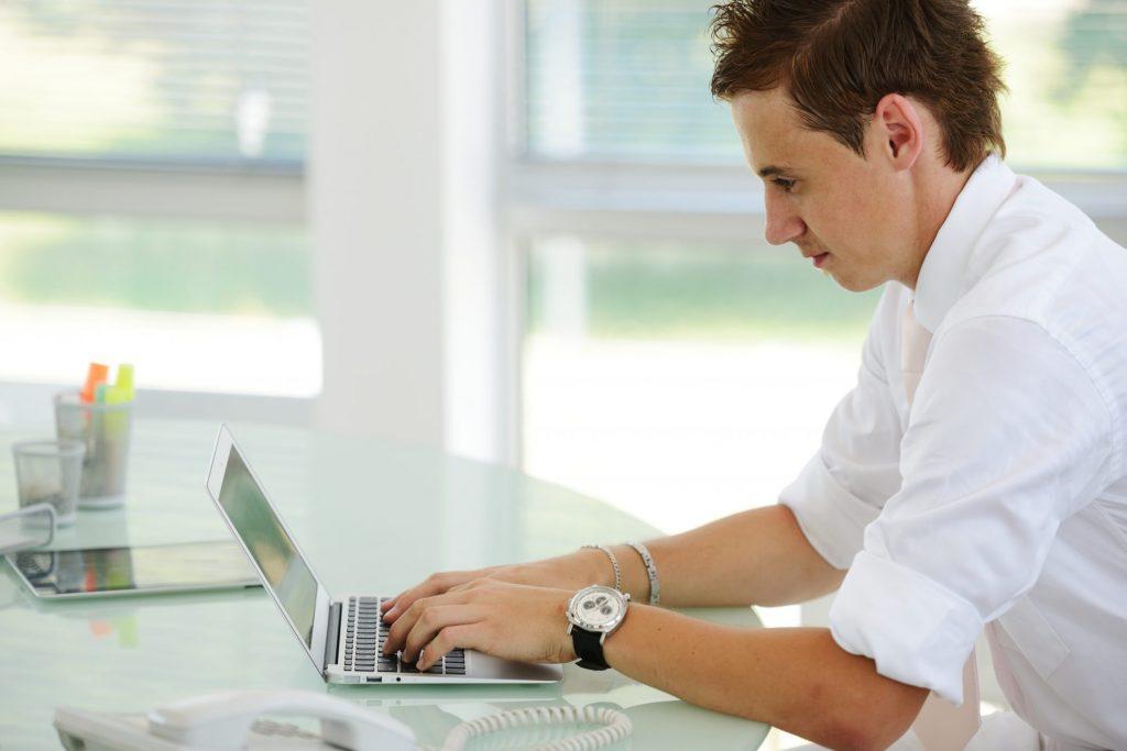 Man sitting at desk paying off bills