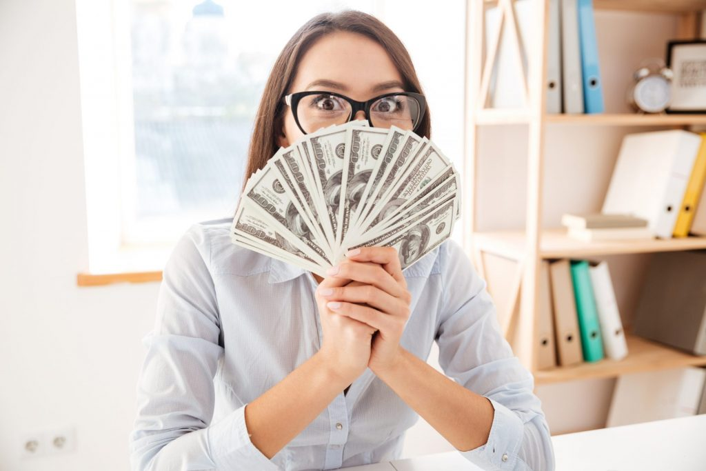 Businesswoman at desk hold money fanned out in hands - Smart Ideas To Take Control of Your Money