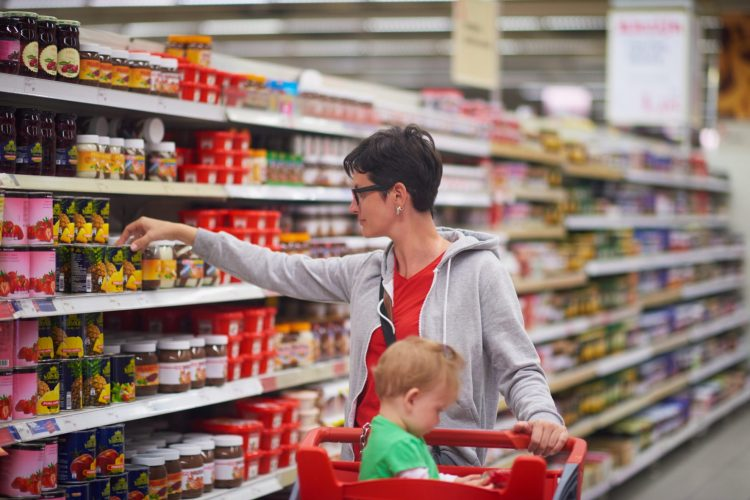 Woman shopping in grocery store with child - coupon lingo