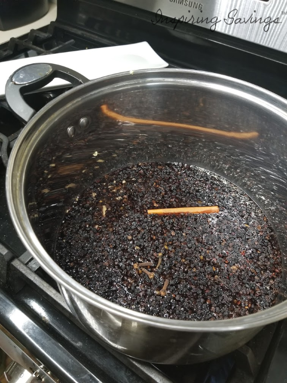 Adding Ingredients for homemade elderberry syrup to pot