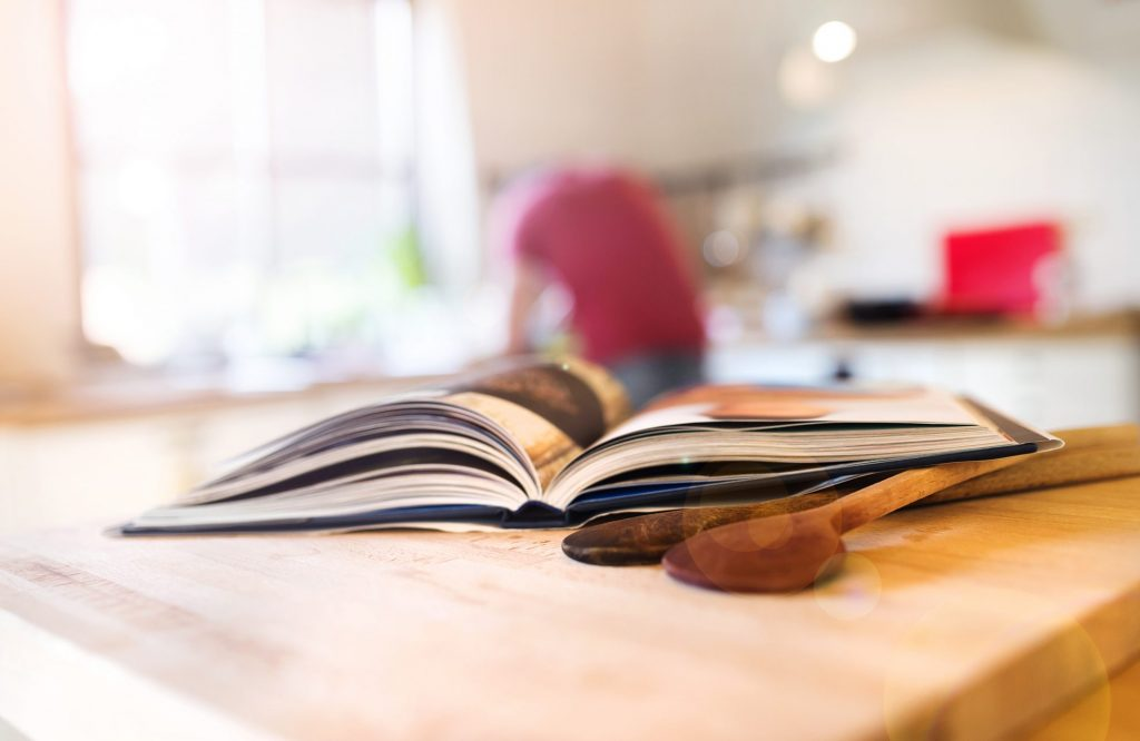 cookbook open with wooden spoons on kitchen island