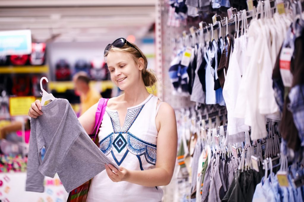 Woman shopping for clothes while on sale