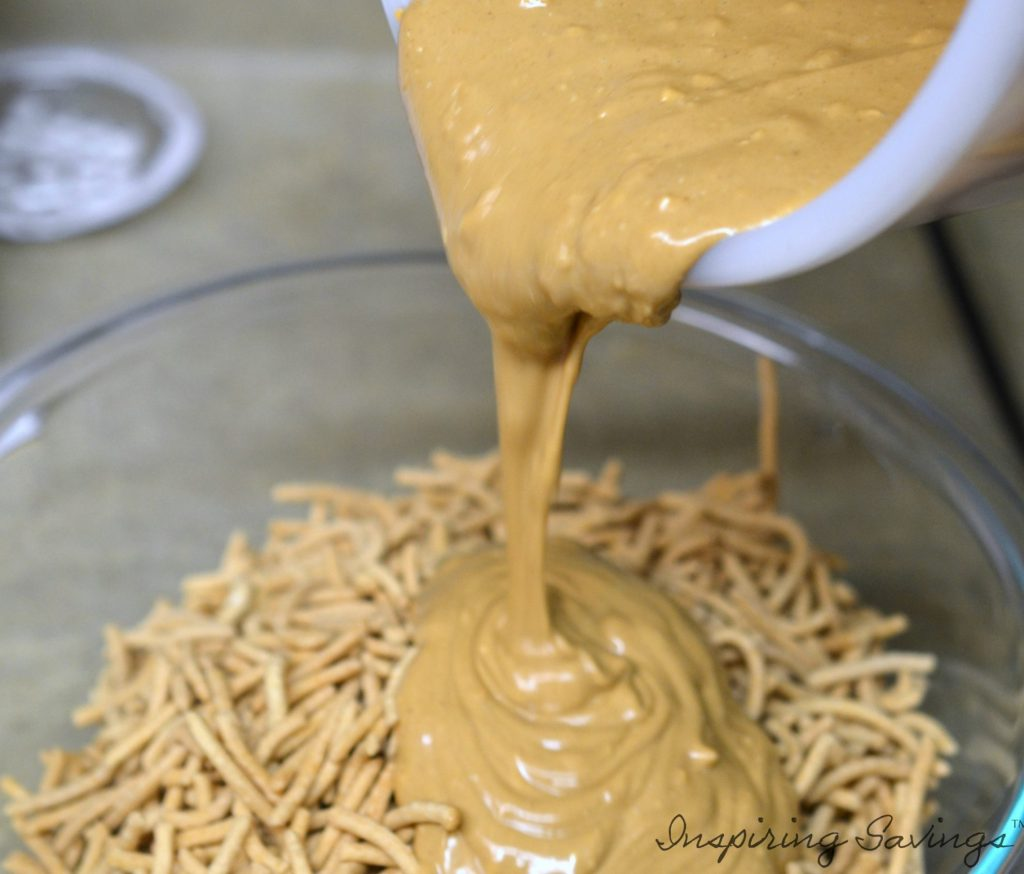 Pouring butterscotch mixture over lo mein noodles to create haystack mummy cookies