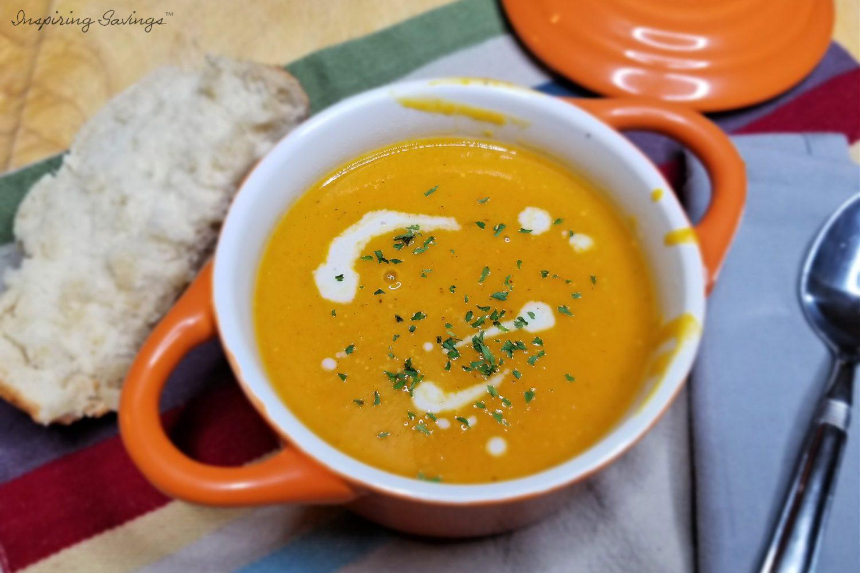 Roasted Butternut Squash Soup in orange crock ready to serve.