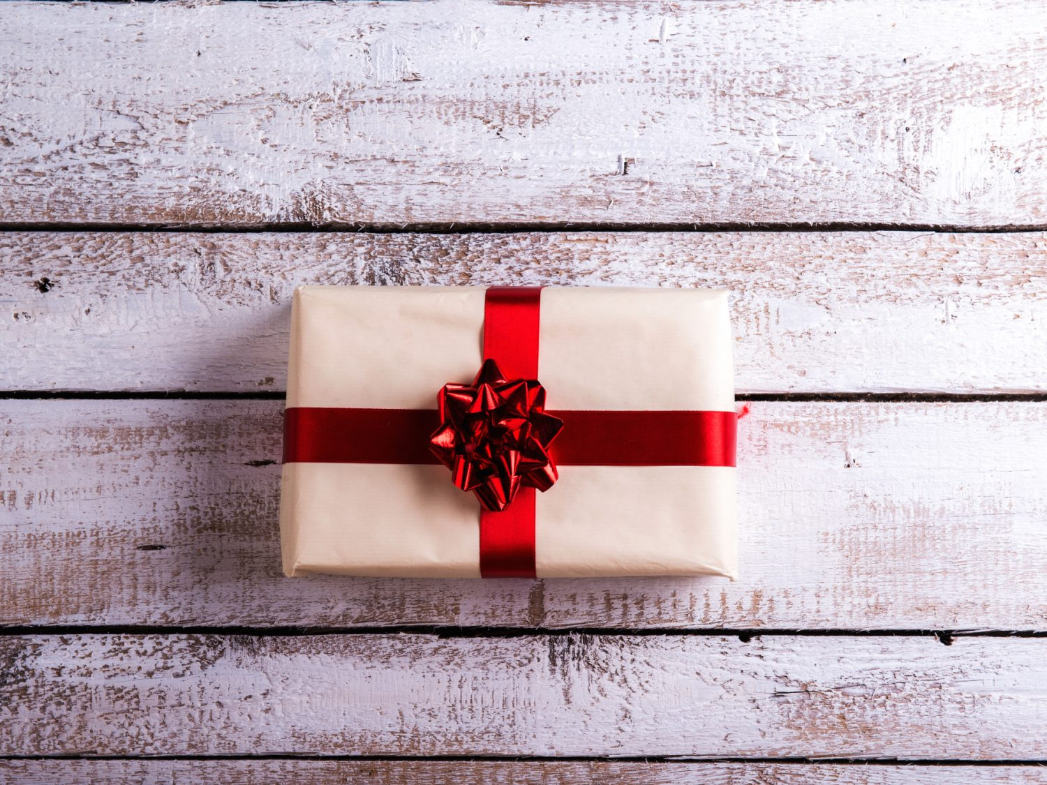 One Christmas Present on white wooden background