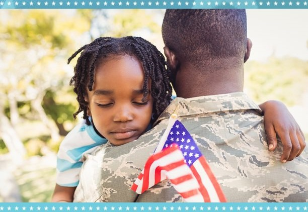 Military dad hold son with flag in hand.