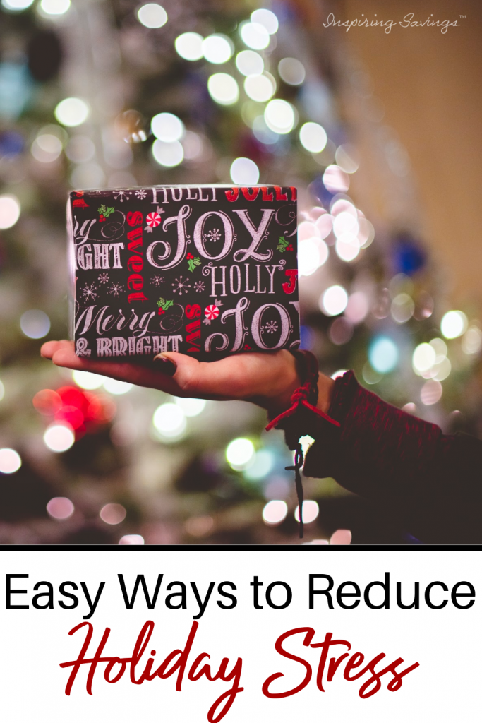 Woman holding package in front of Christmas tree - Easy ways to reduce stress