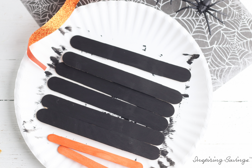 painting popsicle sticks orange and black for witch hat craft