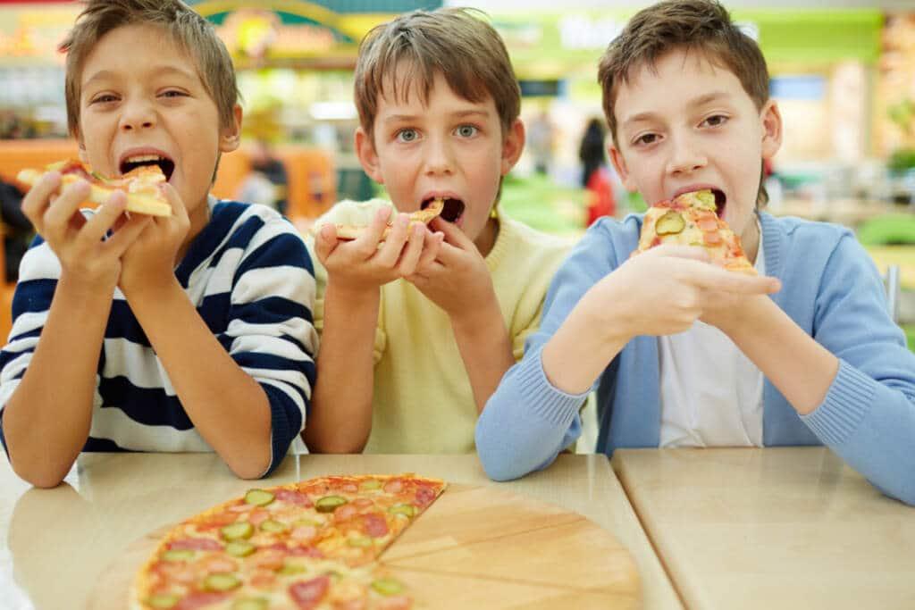 Three boys eating pizza - Kids eat free
