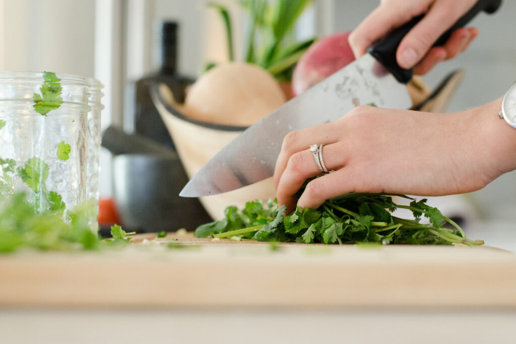 Women chopping up cilantro, Meal prep for freezer cook methond