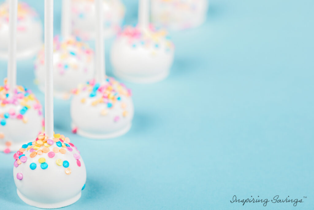 Vanilla Cheesecake cake pops with sprinkles on blue background