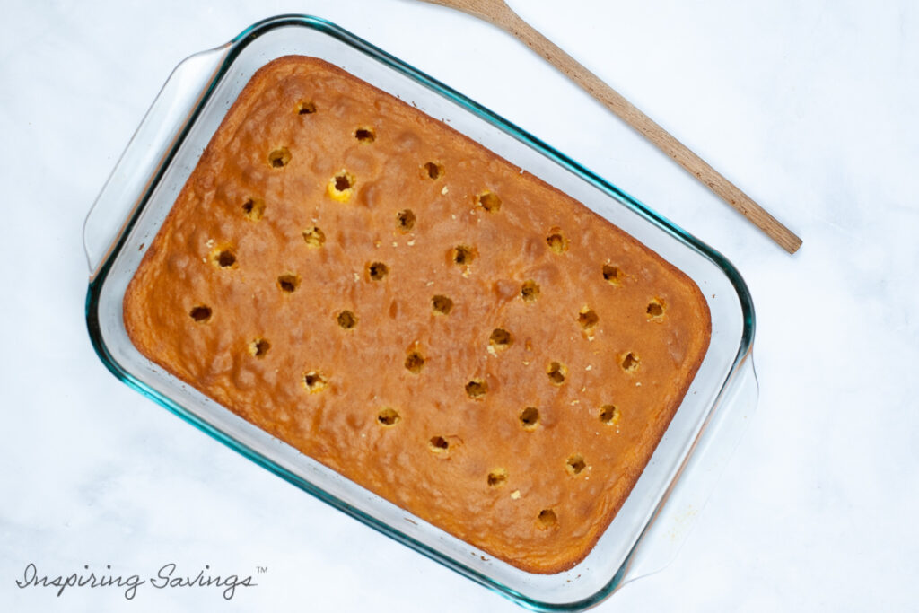 Poked holes in yellow cake for banana pudding pole cake