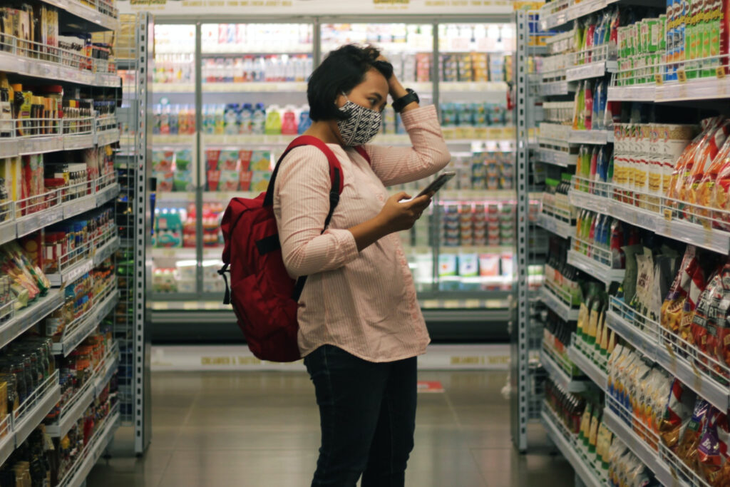 Women using phone in grocery store to find coupon savings