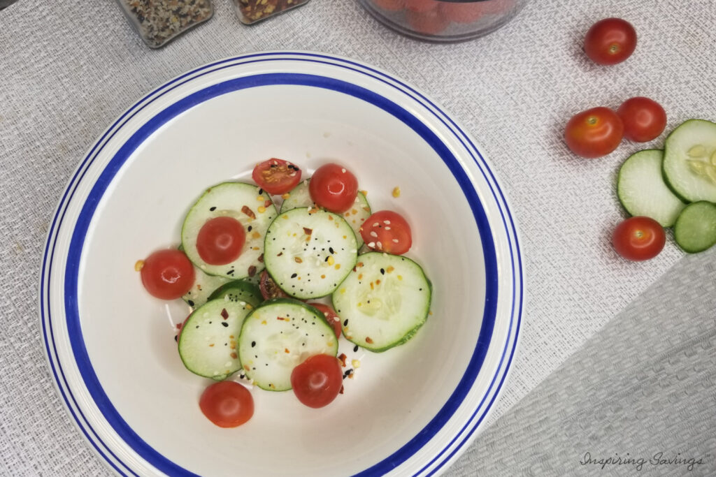 Cucumber tomato salad in white bowl with blue rim