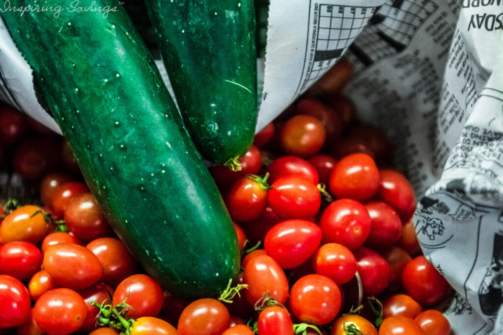 Whole cucumbers and cherries tomatoes in basket with newspaper filling