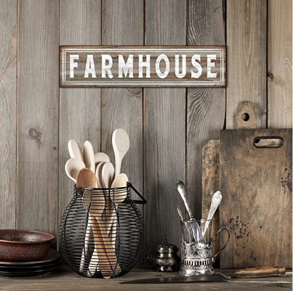Farmhouse sign hanging on wooden wall