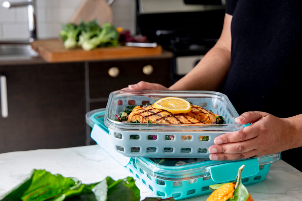 Woman hold glass food containers on counter top for meal prep