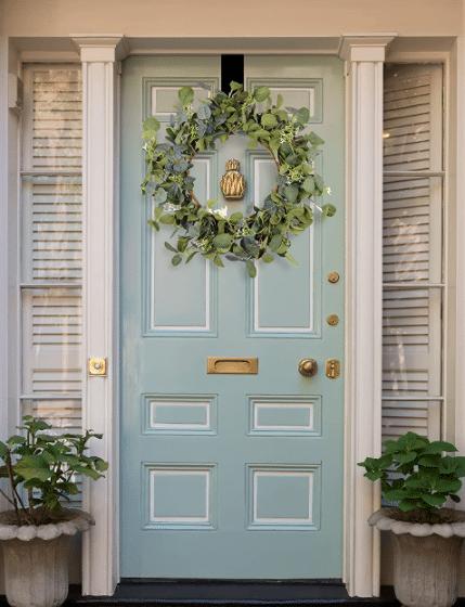 Eucalyptus wreath hanging on teal color door.