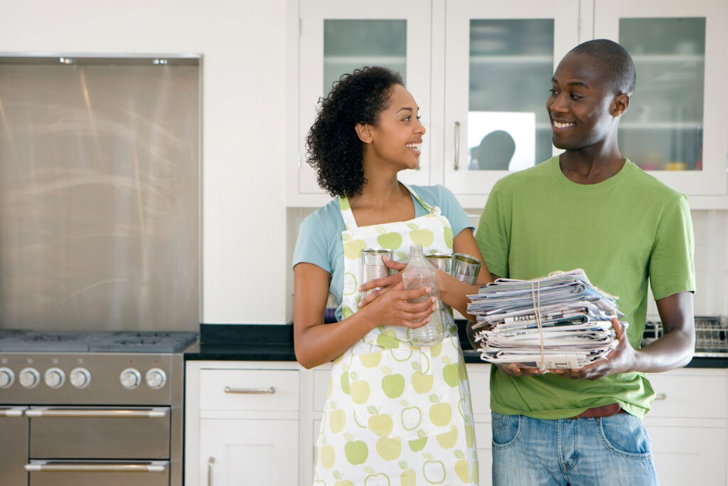 Couple Recycling old Newspaper - standing in kitchen
