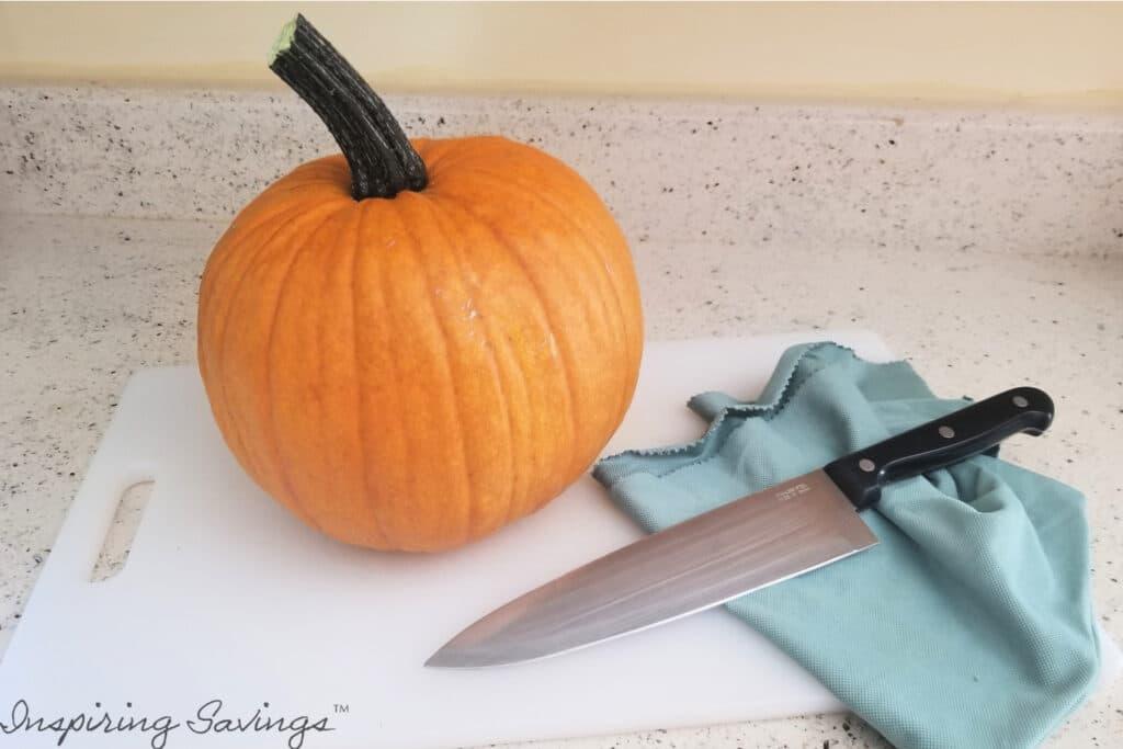pumpkin on cutting board with knife
